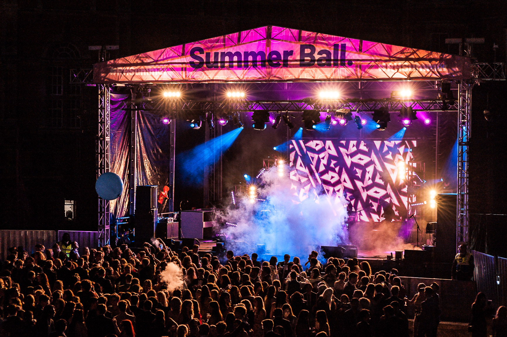 image of Main Stage lit up in pink and purple with smoke at Summer Ball 2019