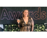 Image of VP Societies & Sport Lucy Brown holding a glass of prosecco in front of the Society Awa